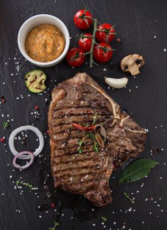 Beef t-bone steak on black stone table