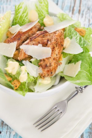 Photo for Caesar salad with chicken and greens on wooden table - Royalty Free Image