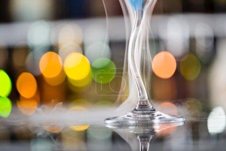 Cocktail with ice vapor on bar desk