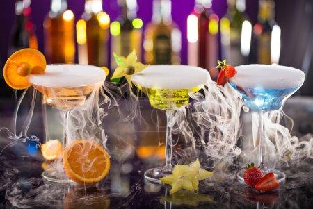 Cocktails with ice vapor on bar desk