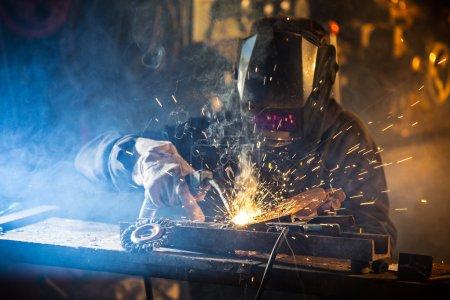 Photo pour Soudeur en action avec des étincelles lumineuses. Construction et fabrication thème . - image libre de droit