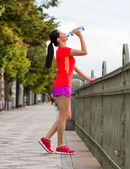 Young woman drinking water after running in the city