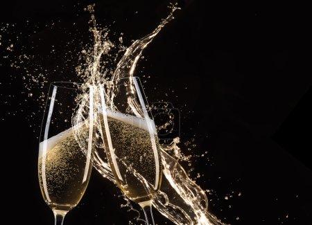 Photo pour Verres de champagne avec éclaboussure, isolés sur noir - image libre de droit