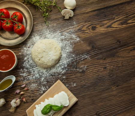 Photo for Italian pizza preparation surrounded by ingredients, top view. - Royalty Free Image