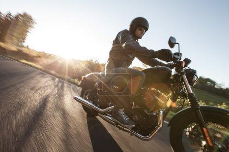 Photo pour Siège homme sur la moto sur la route forestière au lever du soleil . - image libre de droit
