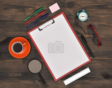 blank clipboard on brown wooden table, top view.