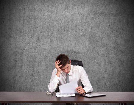 Tired businessman sitting in office and counts los...