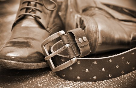 Fashionable leather boots and brown leather belt with gold buckle. Vintage style. Handmade. Autumn and spring shoes