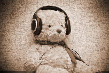 Photo pour Ours en peluche écoutant de la musique sur les écouteurs. Photo de sepia tonique - image libre de droit