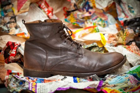Men's leather boots crumpled sheets of colored paper. Autumn - spring shoes in grunge style.