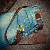 Blue jeans, a leather belt with a buckle and leather jacket