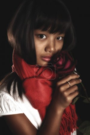 Beautiful brunette girl in a red scarf around his neck, with a red rose in her hand on a black background