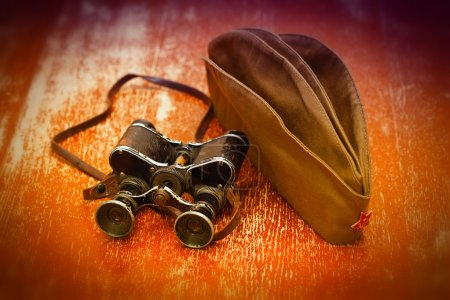Items WWII: military binoculars, soldier field cap. May 9 Victory Day.