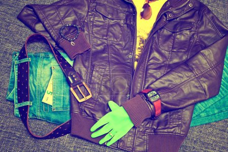 Fashionable clothes: blue jeans with a leather belt, leather jacket, T-shirt, watches, sunglasses, bracelet on the arm, glove, 5 Euro banknote