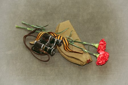Carnation flowers, George Ribbon and military binoculars. Retro photo to Victory Day on May 9
