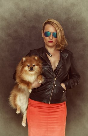 Fashionable woman in a leather jacket, sunglasses and a red skirt keeps the dog in her arms.