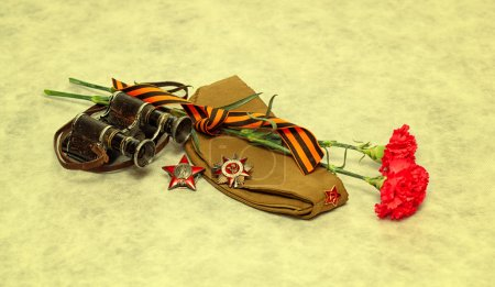 In memory of the Second World War: George Ribbon, forage cap, flowers, medal, the Order of the Red Star, the military binoculars.