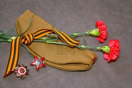 Photo pour Fleurs, oeillets, George Ribbon, médaille et l'ordre de l'étoile rouge, cap de champ - image libre de droit
