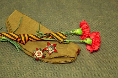 Photo pour Le jour du 9 mai victoire : oeillets, George Ribbon, médaille et l'ordre de l'étoile rouge, le chapeau de garnison militaire - image libre de droit