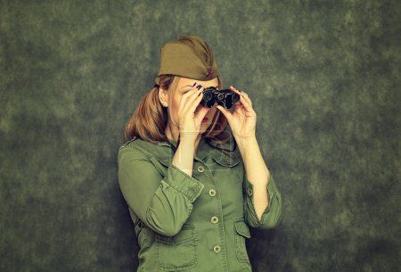 Girl in garrison cap during the Second World War, looking through binoculars. Vintage style. Victory Day on May 9.