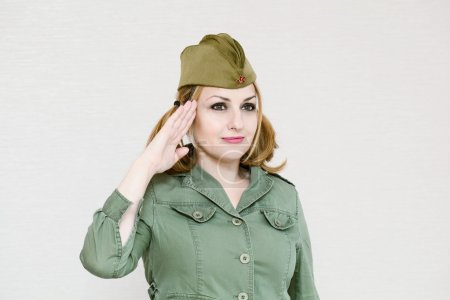 Woman in uniform gives military salute. Girl in garrison cap. In honor of Victory Day on May 9.
