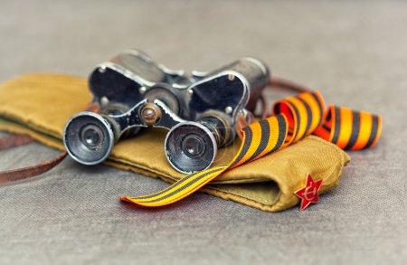 Still life on the Victory day, world war II. Military binoculars, military cap with a star, St. George ribbon