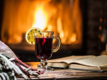 Photo for Hot mulled wine and a book on the wooden table. Fireplace with warm fire on the background. - Royalty Free Image