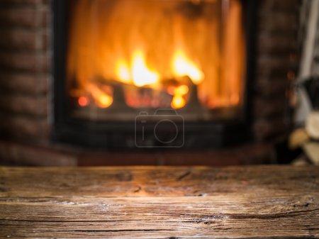 Photo pour Vieille table en bois et cheminée avec feu chaud sur le fond . - image libre de droit