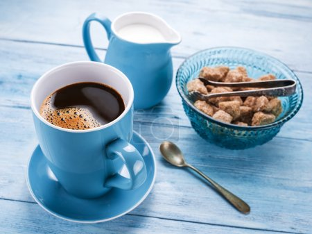 Cup of coffee, milk jug and cane sugar cubes.