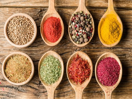 Photo for Assortment of colorful spices in the wooden spoons on the wooden table. - Royalty Free Image