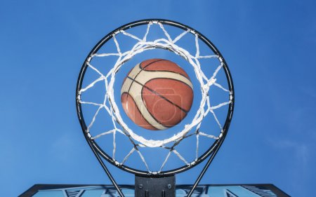 Basketball falling through the net. Blue sky on the background.
