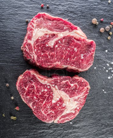 Rib eye steaks with spices on the black background.