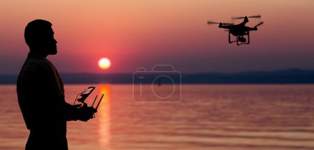 Photo for Man flying a drone near seaside at the sunset. - Royalty Free Image