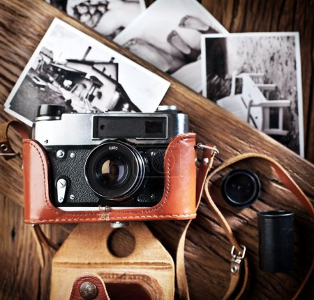 Photo for Old rangefinder camera and black-and-white photos on the old wooden table. - Royalty Free Image