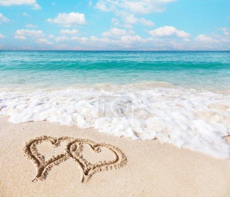 Photo pour Coeurs dessinés sur le sable de la plage. - image libre de droit