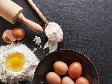 Photo pour Préparation de la pâte. Ingrédients de cuisson : oeuf et farine sur carton noir . - image libre de droit