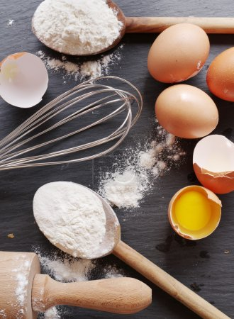 Photo for Dough preparation. Baking ingredients: egg and flour on black board. - Royalty Free Image