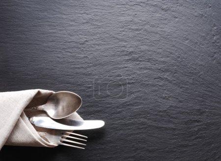 Silberbesteck auf dunkelgrauem Hintergrund.