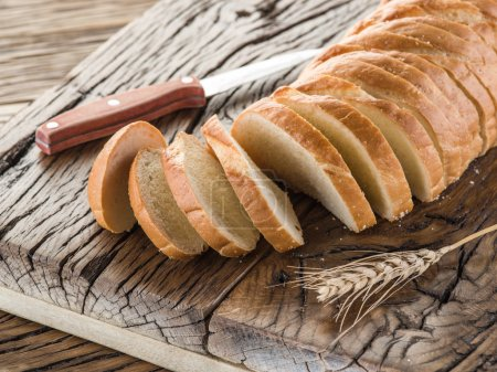 Sliced white bread on the wooden plank.