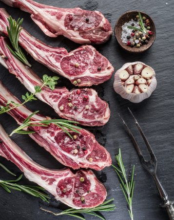 Photo for Raw lamb chops with garlic and herbs on the old wooden table. - Royalty Free Image