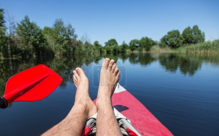 Man's legs over canoe. Resting time.