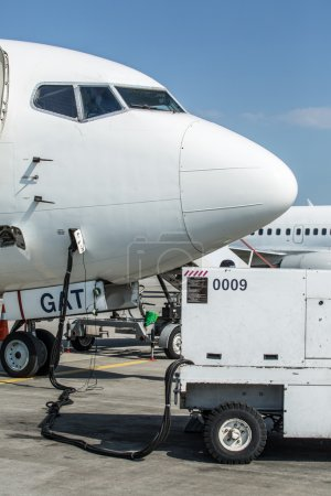 Ground service equipment and airplane in the airport.