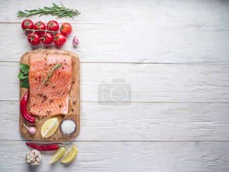 Photo pour Saumon frais sur la planche à découper. Processus de cuisson . - image libre de droit