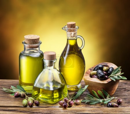 Glass bottles of olive oil and few berries on the wooden table.