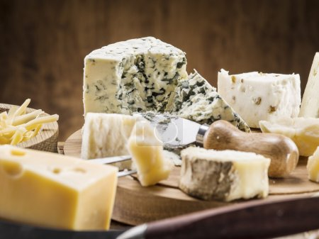 Photo for Variety of cheeses on a wooden board. - Royalty Free Image