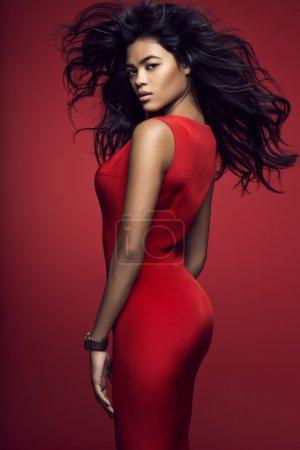 Photo pour Modèle belle mulâtre en robe rouge qui pose en studio - image libre de droit