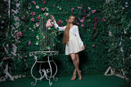 Photo for Fashion and beautiful young woman in a green wall of flowers and leaves - Royalty Free Image
