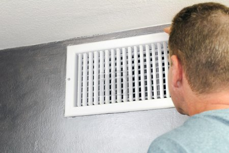 Man Looking in an Air Vent