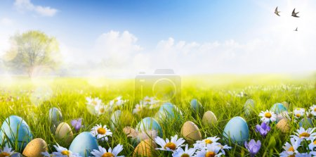 Photo for Colorful Easter eggs decorated with flowers in the grass on blue sky background - Royalty Free Image