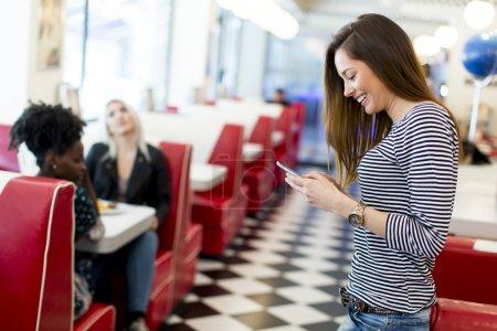 Photo pour Femme avec un téléphone dans le restaurant - image libre de droit